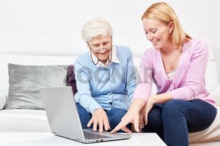 Junge Frau erklärt einer Seniorin einen Laptop