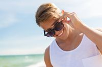 smiling young man in sunglasses on summer beach