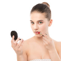 Young brunette woman with perfect clean face applying lipstick using mirror. Isolated on a white.