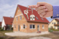 key in hand of real estate agent as offer for new residential home