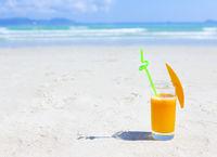 Glass of orange colour juice and sand and sea