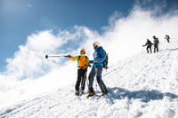 fully equipped Professional climbers descend down the snowy slope in sunny weather