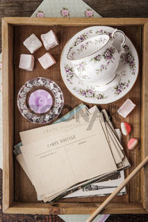 Tea things with sweets and postcards on the wooden tray