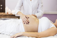 Pregnant woman have massage treatment at spa salon
