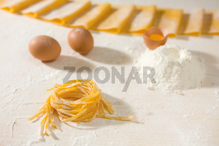Fresh uncooked tagliatelle pasta over a table