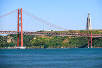 25th of April Bridge suspension bridge over river Tejo with Jesus Christ the King Statue on background in Lisbon. Portugal