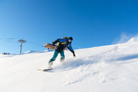 Freeride snowboarder rolls on a snow-covered slope leaving behind a snow powder against the blue sky