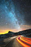 Night landscape. Night sky with a north hemisphere Milky Way and stars. The night road illuminated by the car winds with a serpentine and leaves in a distance to a foot of an acute rock. Light trails of red color. The concept of the path to knowledge and