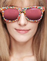 Closeup portrait of young blonde smiling  female with fun candy glasses