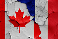 flags of Canada and France painted on cracked wall
