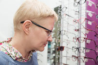 Mature woman chooses new frame for glasses in the store optics