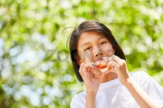 Asiatisches Mädchen isst ein Baguette