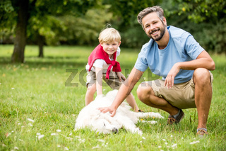 Junge und Vater spielen mit dem Hund