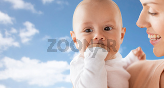 happy mother with baby sucking fingers over sky