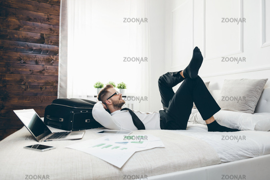 Young businessman on bed working with a laptop from his hotel room