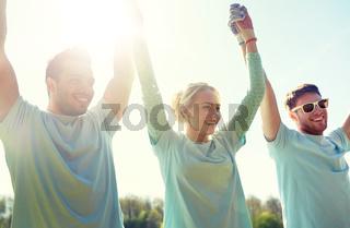 group of happy volunteers holding hands outdoors