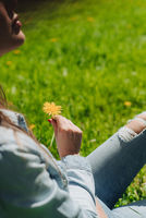 Woman smelling flower sitting on lawn