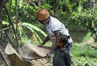 Frau beim Absieben von Reiskörnern, Madagaskar