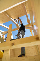 Builders at work with wooden roof construction.