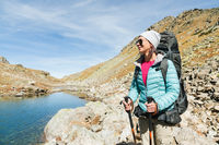 A hiker girl in sunglasses and a hat with a backpack and mountain gear with tracking treks in her hands looks at the beautiful view of a high mountain lake in an archipelago in the northern Caucasus. Karachay-Cherkess Republic