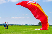 Paragliding instructor with boy testing kite