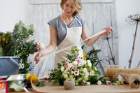 Florist with beautiful bouquet , ribbon,
