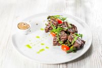 Grilled steak delicious beef meat on a white plate on a light background menu