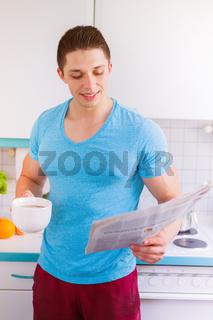 Junger Mann liest lesen Zeitung in der Küche Hochformat morgens Morgen