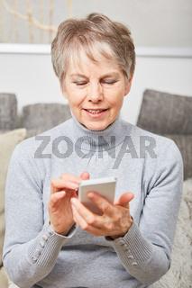 Alte Frau installiert App auf dem Smartphone