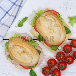 Brötchen Sandwich Baguette belegt mit Käse und Schinken Quadrat von oben auf Holzbrett