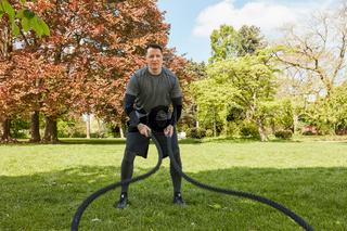 Mann macht Battle Rope Training im Park