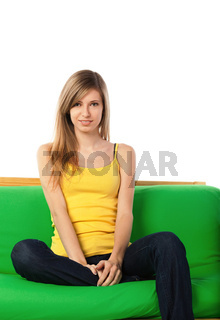 Smiling blond young woman on sofa
