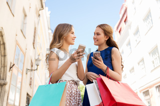 happy women with shopping bags and smartphones