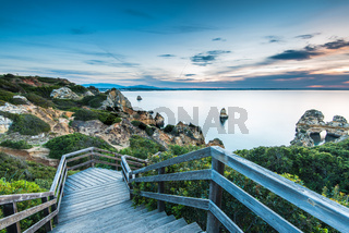 Wooden footbridge walkway to beautiful beach Praia do Camilo on coast of Algarve region, Portugal