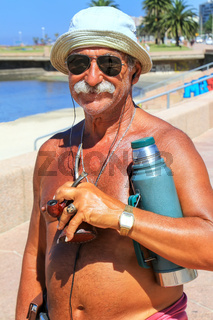 Local man standing with mate cup and thermos at the beach of Rio