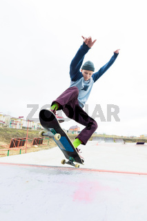 A skateboarder teenager in a hat does a trick with a jump on the ramp. A skateboarder is flying in the air