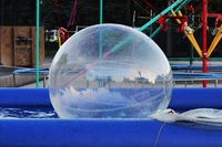 Inflatable small balloon for children on the water in pool. The ball in the water - fascinating summer attractions for children. Water zorbing