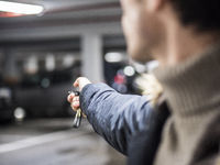 Confident man on parking setting car alarm