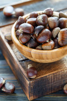 Raw chestnuts in a wooden bowl.