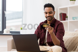 smiling man with laptop and credit card at home