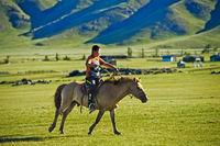 Junge reitet auf einem Pferd durch die Steppe, Orchon-Tal, Mongolei