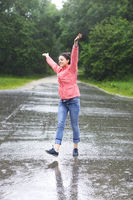 Rain city happy girl jumping in the puddle