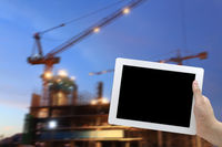 hand hold digital tablet construction site at dusk background