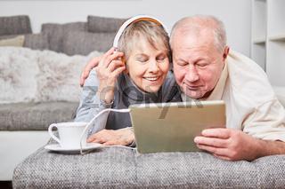 Senioren Paar mit Tablet PC hört Musik