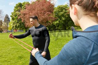 Mann macht Fitnesstraining mit Gummiband