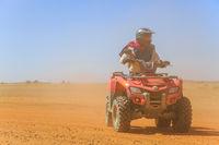 Ait Saoun, Morocco - February 23, 2016: tourist piloting a quad in the Moroccan desert