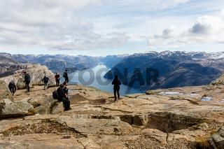 Stavanger, Norway - April 16, 2016: People standing at Preikestolen, the Pulpit Rock. Lysefjorden in the background.