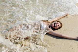 sexy Frau im Bikini liegt im Sand am Strand