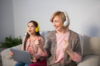 Granny and granddaughter listening music at home