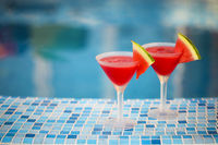 Glasses of watermelon cocktail slices near the pool